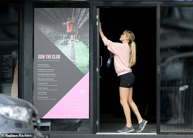 After two months of lockdown, gyms in Brisbane are preparing to open on Monday for 20 people at a time. Pictured: Demi Bertoni, 29, cleaning Club Bunker in Brisbane