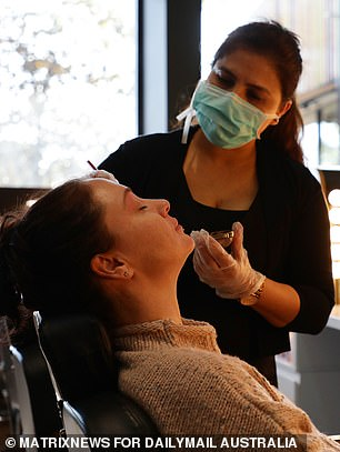 Pictured: A beautician servicing her first client this morning