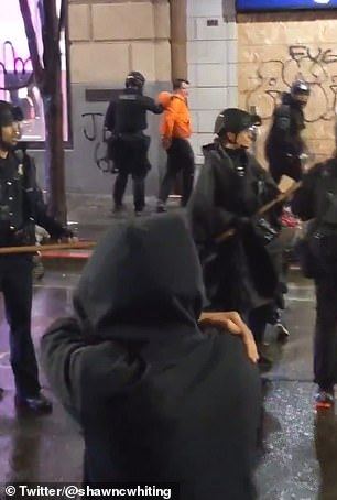 Stunning video captured the moment a Seattle cop removed a fellow officer's knee from the neck of an alleged looter (above in orange) as they arrested him amid George Floyd riots