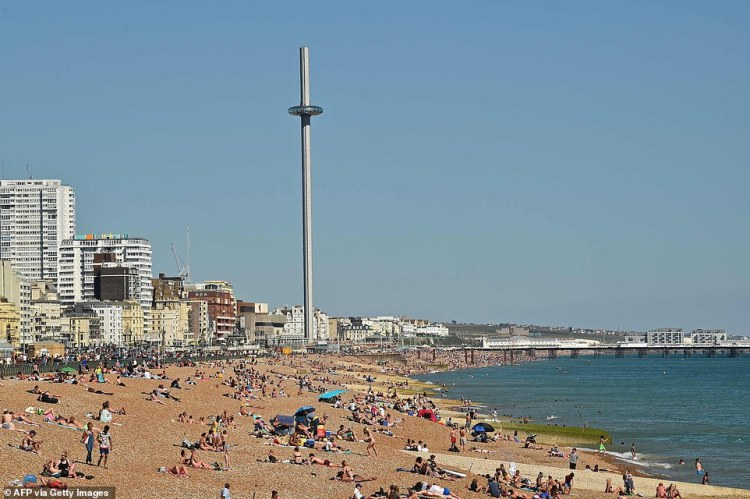 People sunbathe on the beach looking east towards the i360 in Hove, on the south coast of England on May 31, 2020 on the eve of a further relaxation of the novel coronavirus lockdown rules