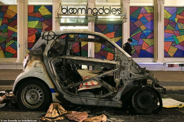 An NYPD car was set on fire outside Bloomingdales. Its torched shell remained there after the looters had passed through the area