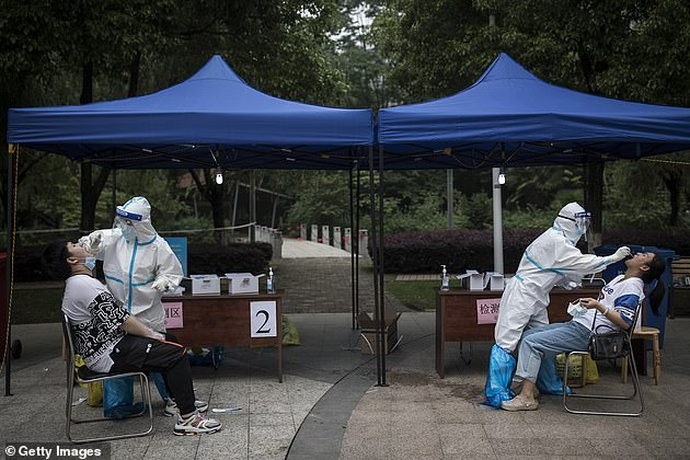 The authorities said that they found 300 COVID-19 infections with no symptoms during the mass-screening. But the chance of those patients infecting others is 'extremely low'. Two medical worker are pictured taking swabs from residents on May 15 in a community in Wuhan