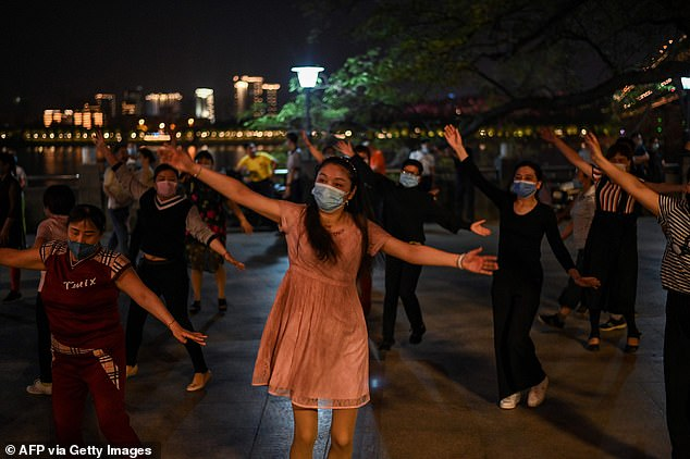Beijing's top health official claimed that 'Wuhan is now the safest city in China' amid the coronavirus pandemic. Residents are pictured wearing face masks as they perform group dance in a park next to the Yangtze River in the former coronavirus epicentre Wuhan