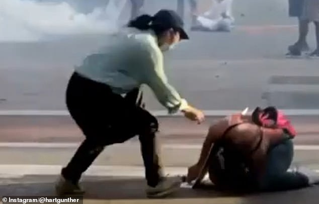 Ratlieff is seen lying on the ground as another protester rushes to help her get away