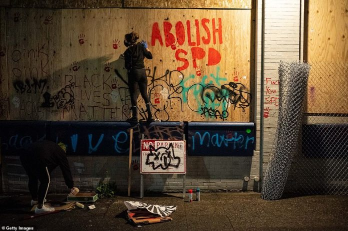Graffiti outside the on-board police compound. The takeover of City Hall on Tuesday came just hours after a Black Lives Matter group sued the city for