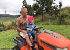 Three-year-old grandson Elijah is pictured on a tractor with Eduard during a visit to South Africa