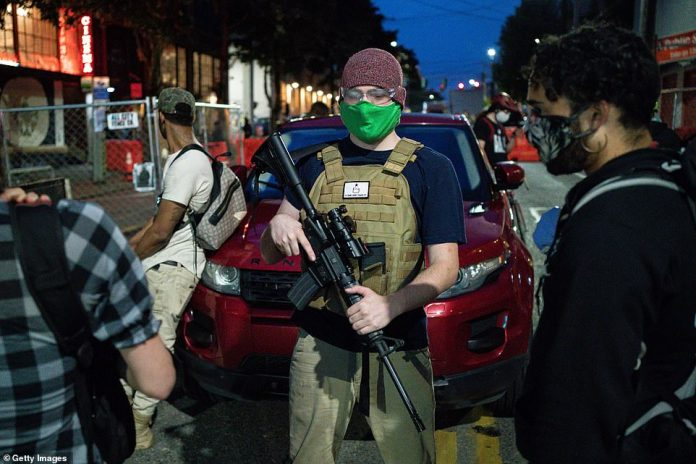 A man carrying an automatic weapon works safely at a checkpoint in the so-called
