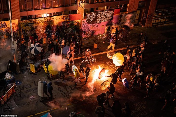 Protesters clash with police near the Seattle East Precinct precinct shortly after midnight June 8. The police abandoned the neighborhood soon after, and the CHAZ was created