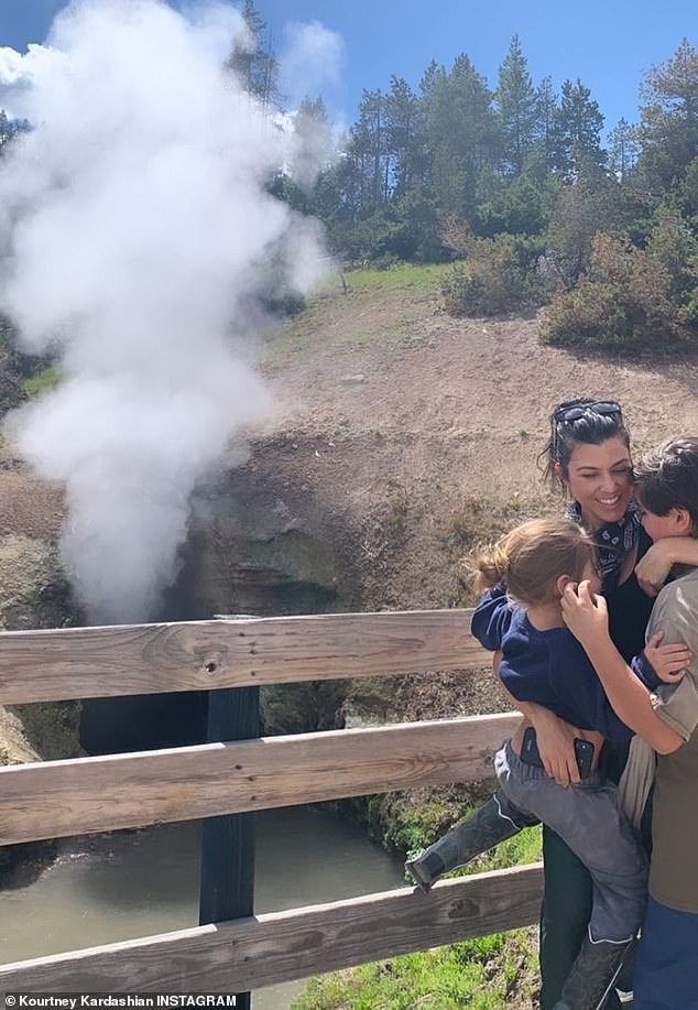Family trip: Kourtney Kardashian shared this sweet snap hugging her boys Mason and Reign while visiting hot springs in Montana on Friday