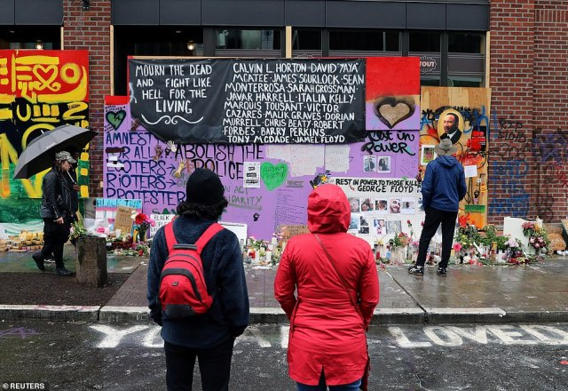 People look at a memorial site of protesters killed during recent violence within the Seattle CHAZ
