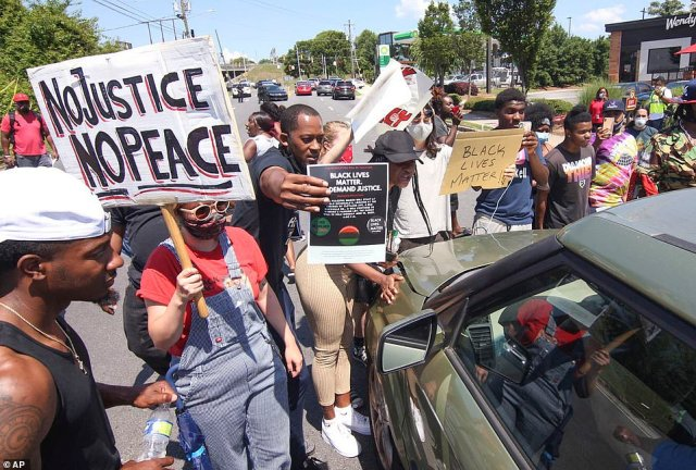 Protesters block University Avenue outside the Wendy's fast food restaurant in Atlanta on Saturday. Hours earlier, a 27-year-old black man was fatally shot by police officers as he was running away