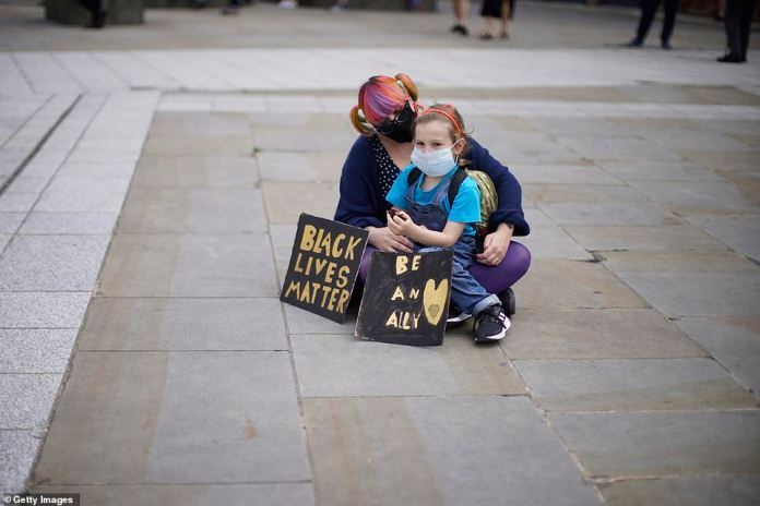 A woman and child sitting with placards at a Black Lives Matter rally in Millennium Square in Leeds this afternoon, joining thousands