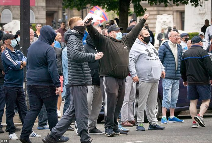 Protesters stand at a demonstration organized by the Loyalist Defense League in George Square in Glasgow this afternoon