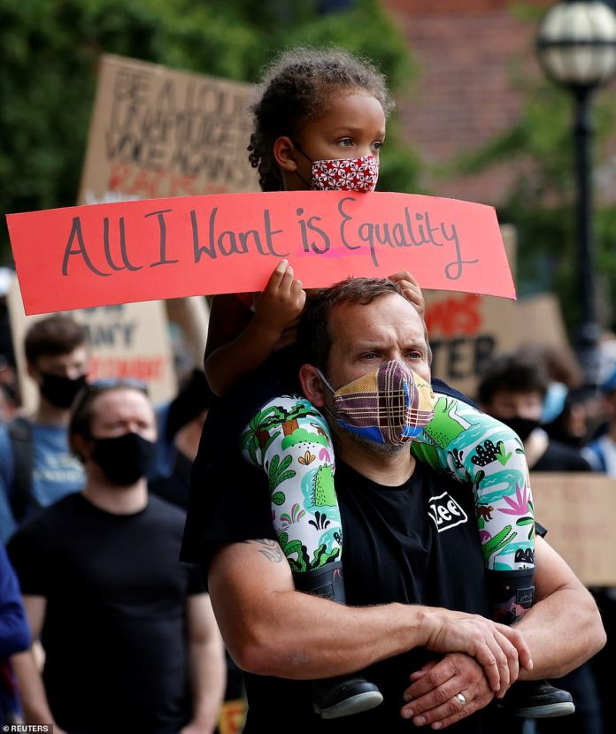 A girl seated on the shoulders of a man holds up a sign saying 'All I want is equality' at a protest in Leeds this afternoon