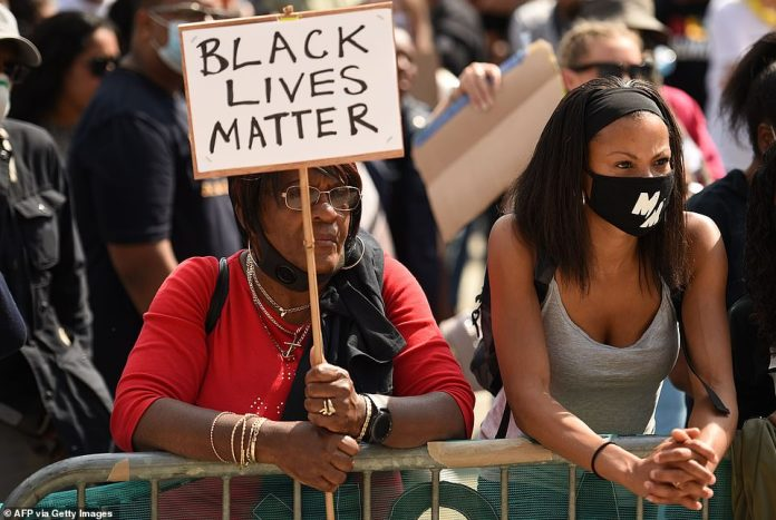 A protester holds up a sign at a rally in support of the Black Lives Matter and Black Voices Matter in central Leeds