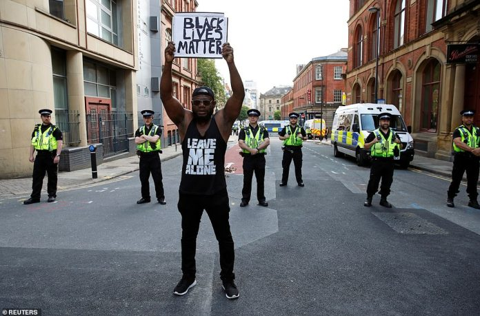 A protester stands in front of the police holding a Black Lives Matter sign in Leeds this afternoon during a peaceful demonstration