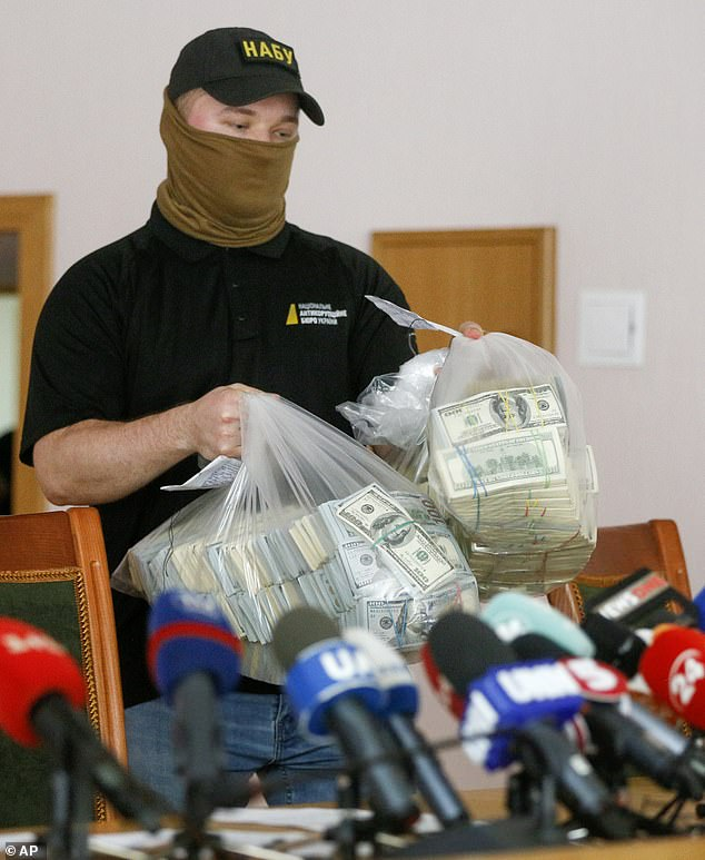 Police officers are seen holding stacks of $100 bills inside clear plastic bags during briefing