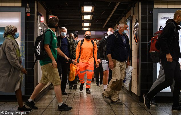 Commuters wear face masks as they pass through Vauxhall underground station on the first day of their mandatory use
