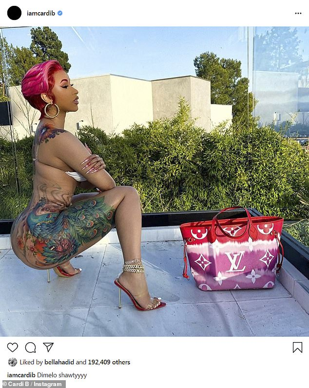 New look: Cardi posed without bottoms and wearing a fuchsia wig that matched her Louis Vuitton bag.'Dimelo [tell me] shawtyyyy,' she captioned the snap, which showed off her tattoo