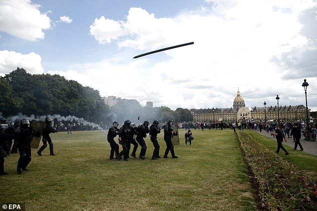 Riot police used teargas and baton charges as they fought with protesters by Les Invalides in the centre of the city on Tuesday afternoon. Pictuerd: A projectile being fired at police by protesters