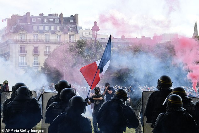 One protester wielded a giant French flag as he faced off against the police