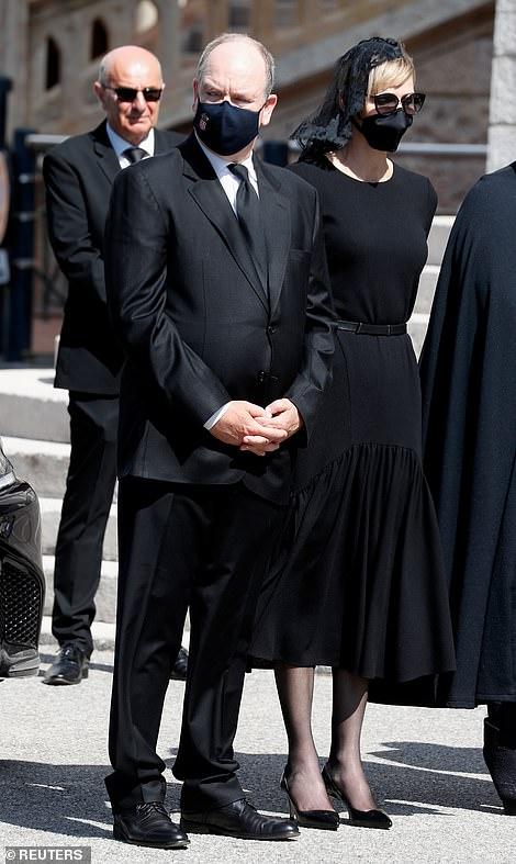 La princesse Charlene, photographiée ci-dessus avec son mari, a opté pour une élégante robe noire avec une ceinture assortie pour les funérailles
