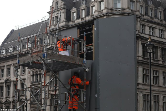 Two workers wearing protective gear climb on scaffolding as they slowly begin to remove the planks around Sir Winston