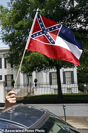 In this April 25, 2020 photo, a participant holds up a small Mississippi state flag during a 'reopening of Mississippi' protest as they pass the Governor's Mansion in the background, in Jackson, Mississippi.  This current flag bears the Civil War era Confederate battle flag design on the canton side of the banner, which has been the center of a simmering debate over its removal or replacement