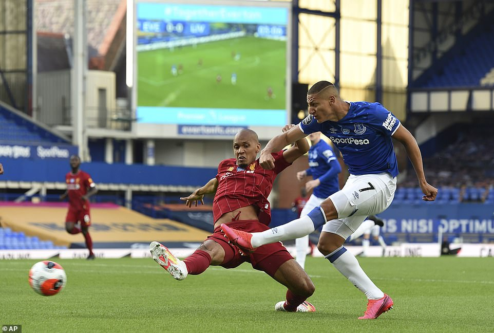 Everton's Richarlison goes for goal in the first half of the game while being closed down by Liverpool midfielder Fabinho
