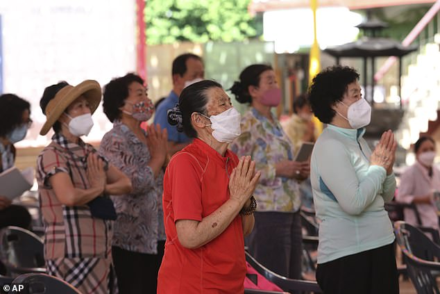 People wearing masks to protect against the spread of the new coronavirus pray during a service at the Chogyesa temple in South Korea today