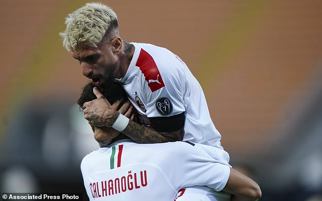 AC Milan's Samu Castillejo, top right, celebrates with teammate Hakan Calhanoglu after scoring during the Serie A soccer match between Lecce and AC Milan, at the Via del Mare stadium in Lecce, Italy, Monday, June 22, 2020. (Spada/LaPresse via AP)