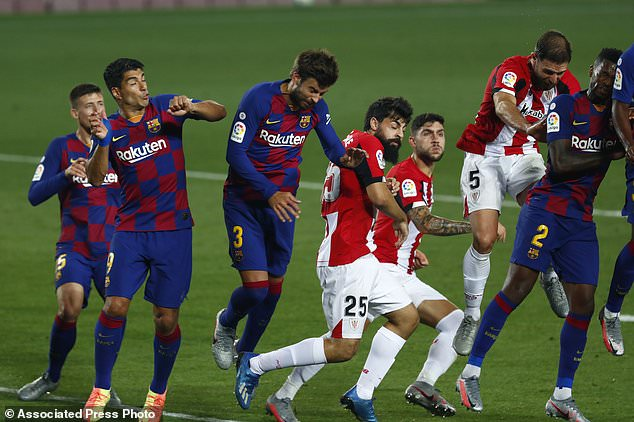 FC Barcelona and Athletic Bilbao players during the Spanish La Liga soccer match between FC Barcelona and Athletic Bilbao at the Camp Nou stadium in Barcelona, Spain, Tuesday, June 23, 2020. (AP Photo/Joan Monfort)