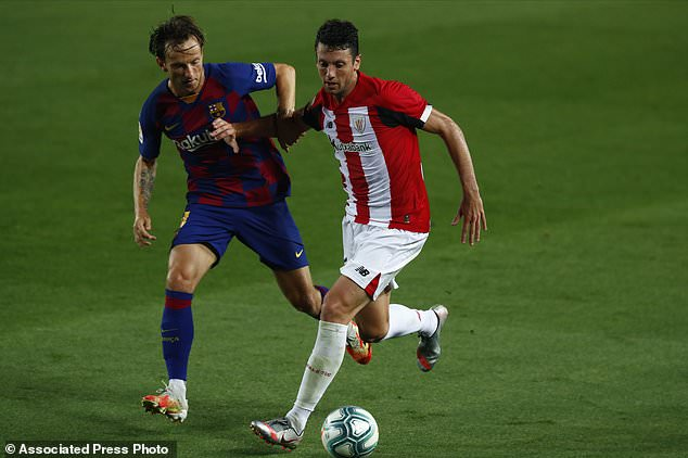 Barcelona's Ivan Rakitic, left, vies for the ball with Athletic Bilbao's Mikel San Jose during the Spanish La Liga soccer match between FC Barcelona and Athletic Bilbao at the Camp Nou stadium in Barcelona, Spain, Tuesday, June 23, 2020. (AP Photo/Joan Monfort)
