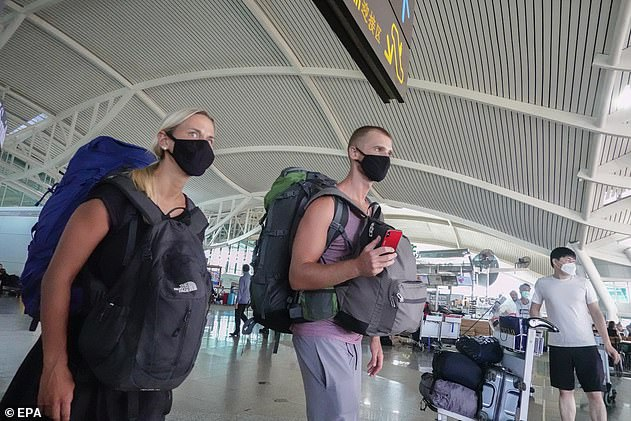 Travellers would face 'strict health protocols' but the move would ideally revive domestic tourism (pictured:Passengers wear protective masks as they depart Ngurah Rai International Airport in Bali in March)