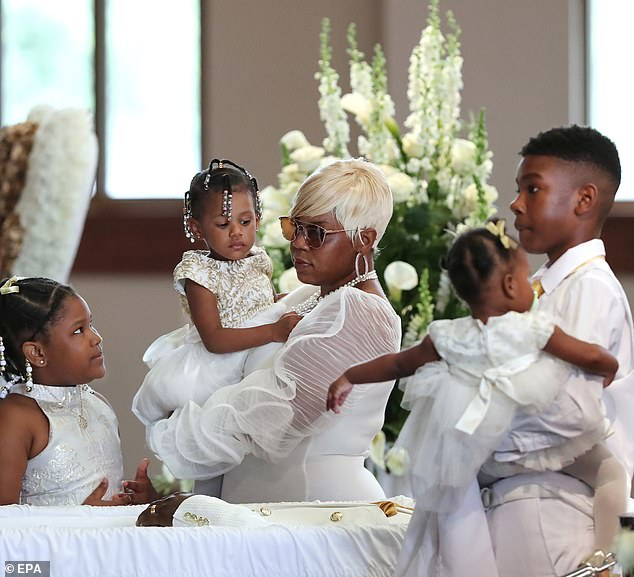 Brooks' wife Tomika Miller, holding one of their children, at his funeral on Tuesday with the rest of their children