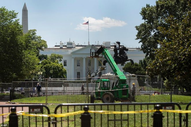 Workers remove part of the cannon at the base of the equestrian statue of Andrew Jackson