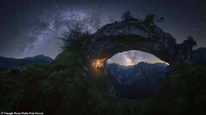 'Double Arch by Pablo Ruiz García.Picos de Europa – Spain. This arch-shaped rock formation is located in 'La Hermida' gorge, in the Picos de Europa mountain range in Spain.Pablo Ruiz García said: 'At first, my initial idea was to capture the galactic center inside the arch, but finally, I decided to shoot the two arches overlapped at this time of the year (late spring) when the Milky Way is still not too high in the sky'