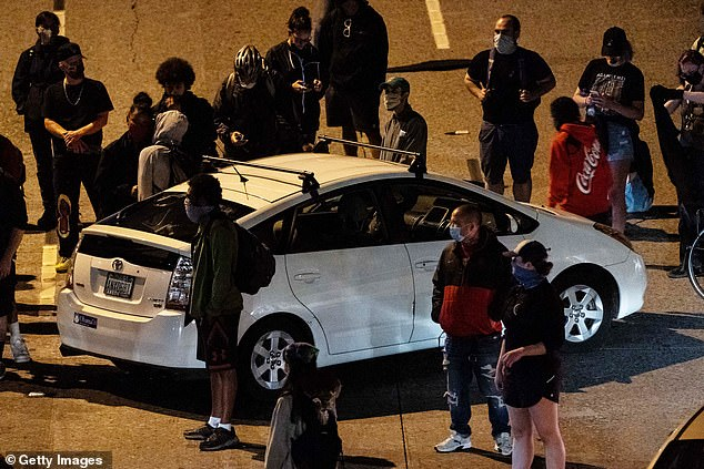 Pictured: Protesters surround a car as they block Interstate 5 after marching from the area known as the Capitol Hill Organized Protest (CHOP) on June 24, 2020 in Seattle, Washington