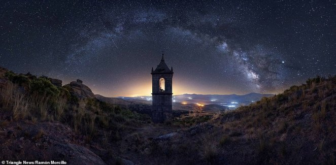 'Enchanted Monastery' by Ramón Morcillo.Ávila – Spain. This image captures the Milky Way arch above a bell tower.Morcillo, who is pictured in the tower, said: 'The monastery was an Augustinian convent founded in 1504 and called the Monastery of Our Lady of the Crag. A few hundred miles drive followed by a long walk and a challenging climb and bushwhack ended in this beautiful and magical place. The icing on the cake was to subtly illuminate the upper part of the bell tower and place myself in one of the windows to create this panorama composed of 14 sky/ground photographs and get a very special result'