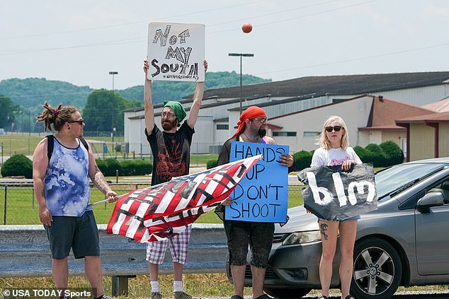 A small number of Black Lives Matters supporters were seen lining the streets of Talladega on Sunday and waving the American flag. One demonstrator held a sign that read 'Not My South'