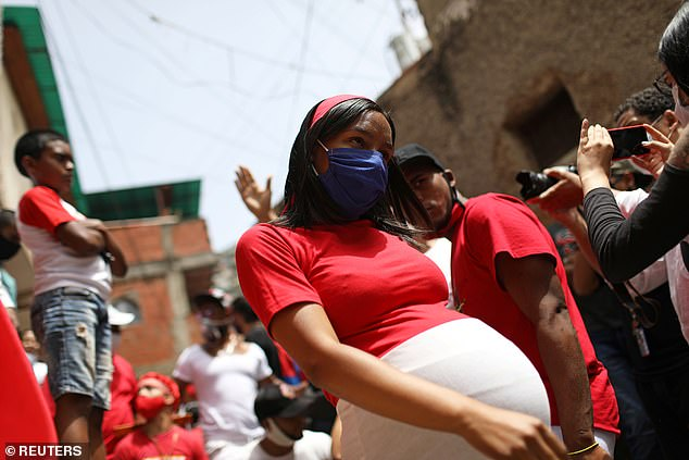 More than 31% of pregnant women were hospitalized compared to 6% of non-pregnant women, putting mothers-to-be at a five times greater risk. Pictured:A pregnant woman takes part in the feast of Saint John the Baptist's Day in San Agustin, Venezuela, June 24