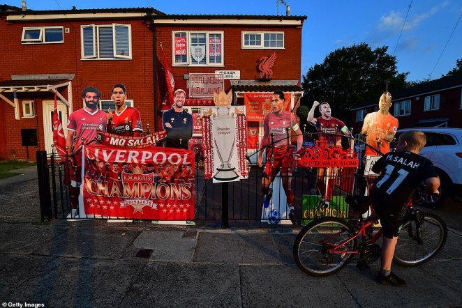A young boy in a Mohammed Salah shirt looks at a house heavily decorated in flags and cardboard cut-outs of the players