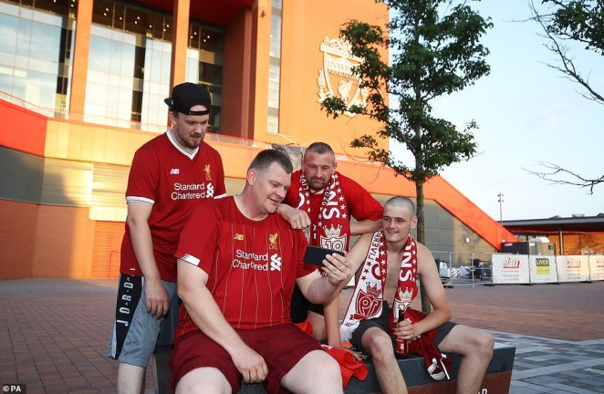Liverpool fans watch the Premier League match between Chelsea and Manchester City on their phone outside Anfield