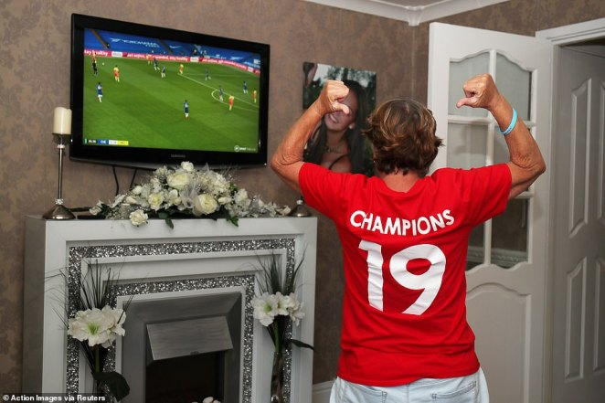 Liverpool fan Emily Farley celebrates after Chelsea take the lead against Manchester City as she watches the match on TV at home