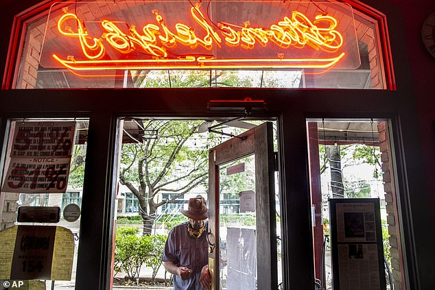 Owner Tom Garrison prepares to close his bar, Stoneleigh P, in Dallas on Friday