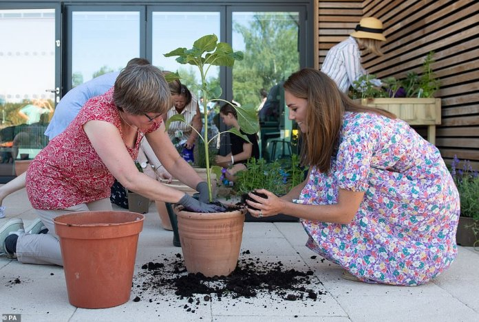 Duchess of Cambridge helps potted plants and herbs during a visit to a children's hospice to help create a new garden