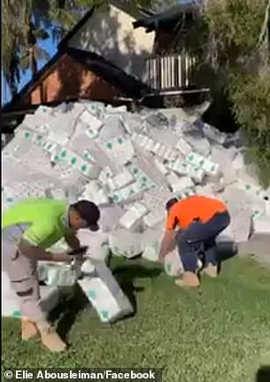 The trio filmed themselves picking up 48-packs from the mountain of toilet paper piled high outside the home in Macquarie Fields in Sydney's south west