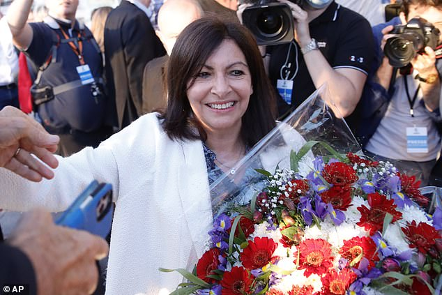 Paris mayor Anne Hidalgo gets a bouquet of flowers after her victorious second round of the municipal election, Sunday