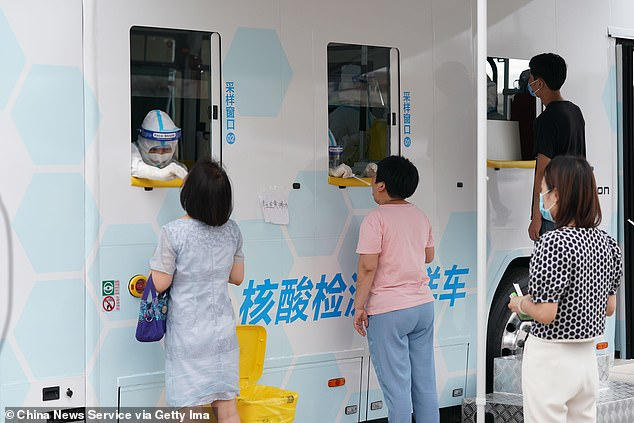 Beijing¿s freak hailstorm came just three days before China put half a million people into a strict Wuhan-style lockdown after Beijing recorded a surge in cases. Medical workers swab throat of people for nucleic acid testing at a testing site for the coronavirus in Beijing