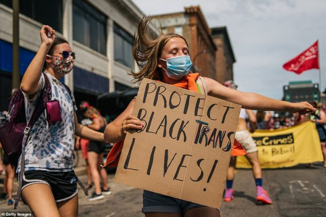 People dance in front of the Minneapolis First Precinct during a Pride march held on Sunday